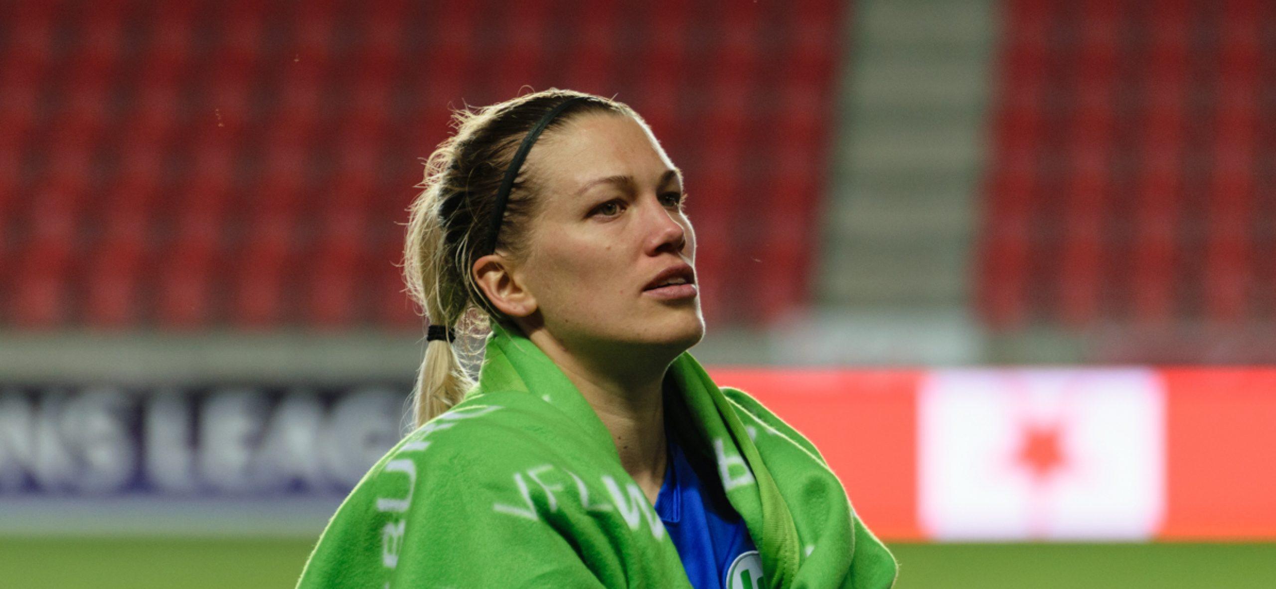 Lara Dickenmann enveloppée dans une couverture aux couleurs et logo de Wolfsburg