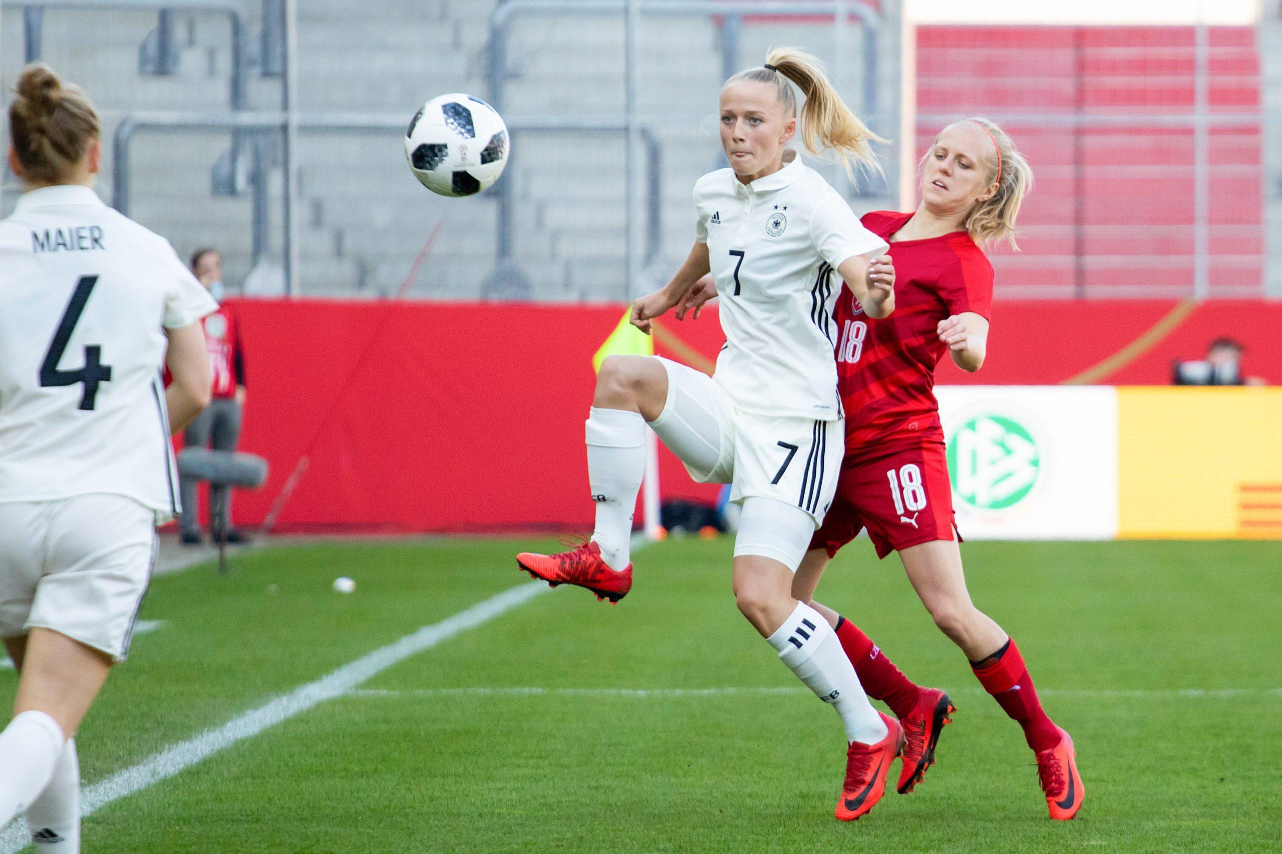 Lea Schuller en maillot de l'Allemagne contrôlant le ballon dans les airs. Une joueuse adverse la couvre dans son dos.